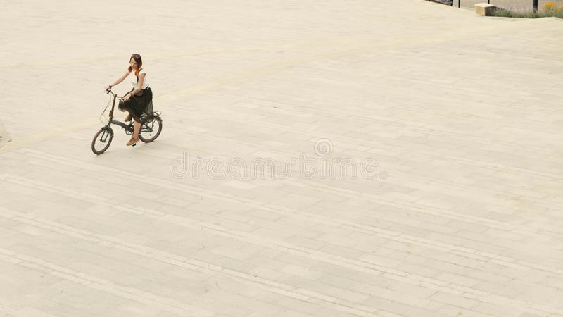 骑自行车的妇女骑自行车者在被铺的路在正方形在夏日 库存图片