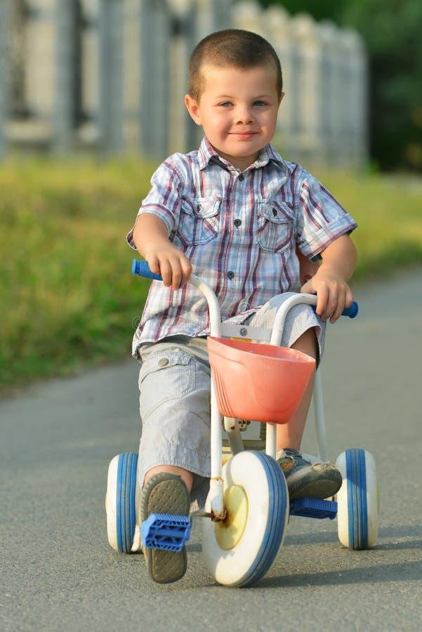 骑自行车的孩子在街道 免版税库存图片