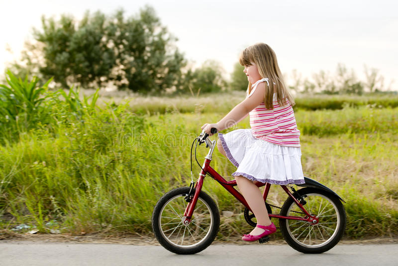 骑自行车的孩子在街道 免版税库存照片