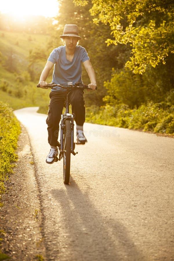 骑自行车的少年在被日光照射了路的夏天 图库摄影