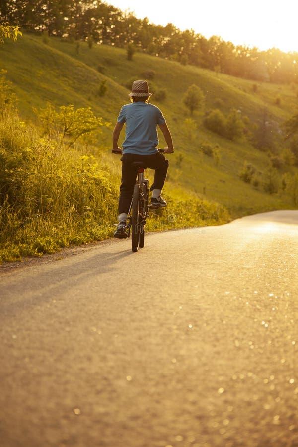 骑自行车的少年在被日光照射了路的夏天 库存照片
