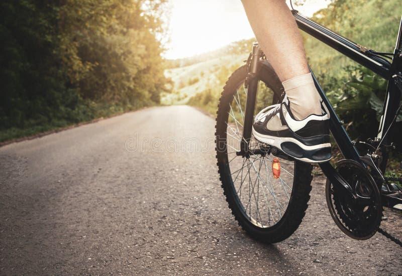 骑自行车的少年在被日光照射了路的夏天 免版税库存图片
