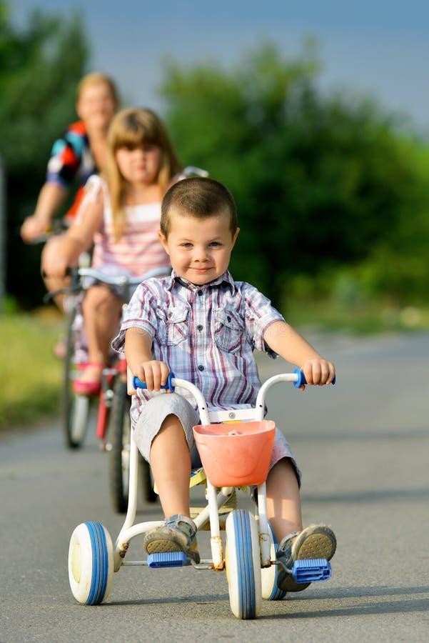 骑自行车的母亲和孩子 库存图片