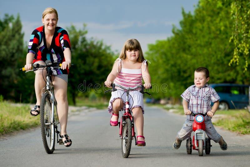 骑自行车的母亲和孩子 库存照片