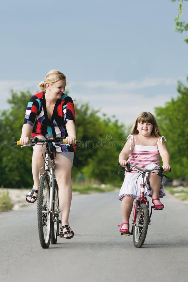 骑自行车的母亲和孩子 免版税库存图片