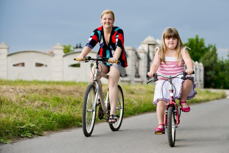 骑自行车的母亲和孩子 免版税库存照片