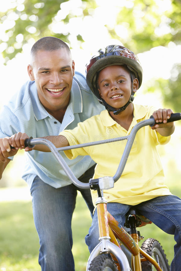 骑自行车的父亲教的儿子在公园 库存照片