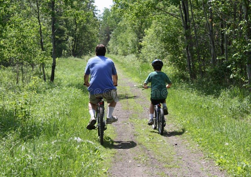 骑自行车的爸爸儿子 图库摄影