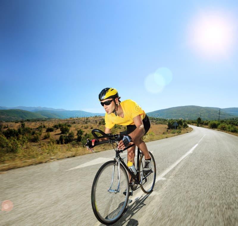 骑自行车的男性骑自行车者在一条开放路在一个晴天 库存照片