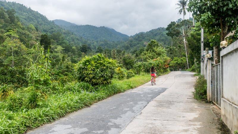 骑自行车的红色短裤的女孩 免版税库存照片