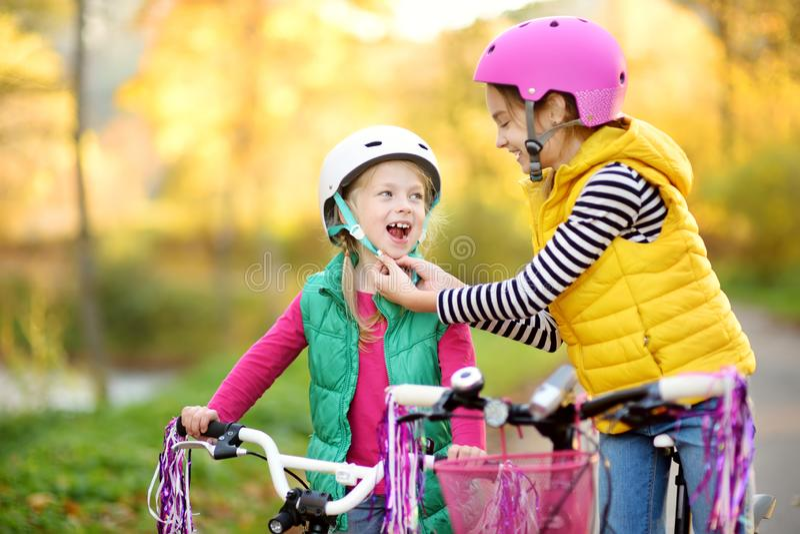 骑自行车的逗人喜爱的妹在城市公园在晴朗的秋天天 r 库存图片