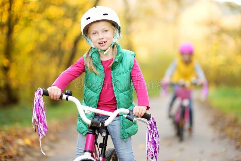 骑自行车的逗人喜爱的妹在城市公园在晴朗的秋天天 r 库存照片