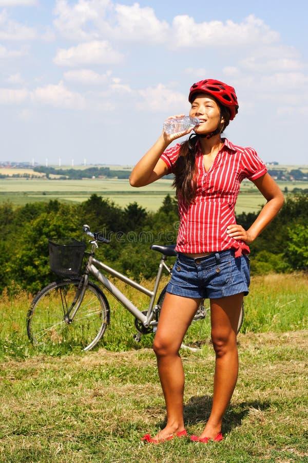 骑自行车的饮用水妇女 免版税库存图片
