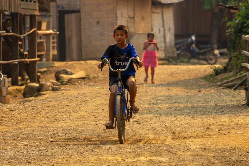 骑自行车老挝的村庄孩子 免版税图库摄影