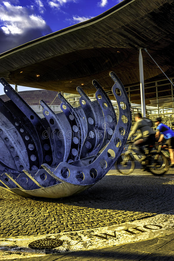 骑自行车者乘坐通过在加的夫海湾的Senedd 免版税库存图片