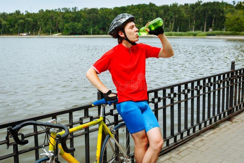 骑自行车者喝从瓶的水 在背景湖 库存图片