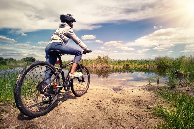 骑自行车者在湖岸站立在明亮的太阳下 免版税库存照片
