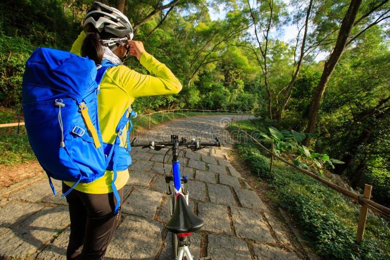 骑自行车者调整盔甲传送带,在骑登山车在森林足迹前 免版税库存照片