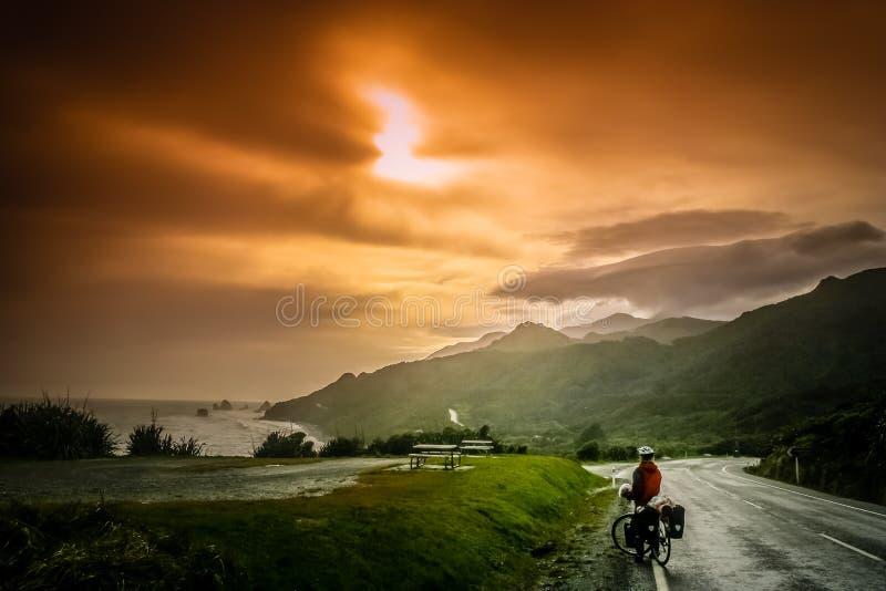 骑自行车者赞赏的日落 免版税库存图片