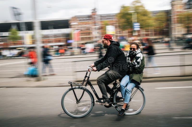 骑自行车者运载自行车行动迷离的,阿姆斯特丹少妇 免版税库存图片