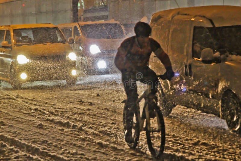 骑自行车者,当驾驶在汽车一般流程的一条积雪的路在晚上时 免版税库存图片