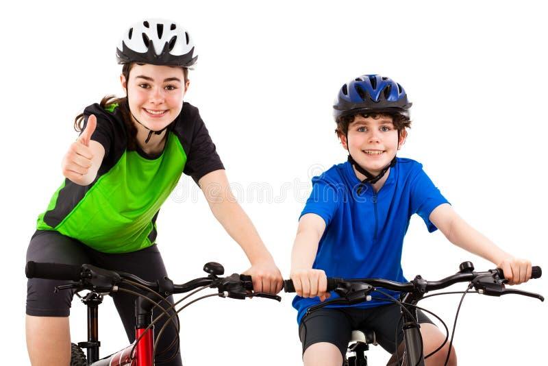 骑自行车者-在白色和女孩隔绝的男孩 图库摄影