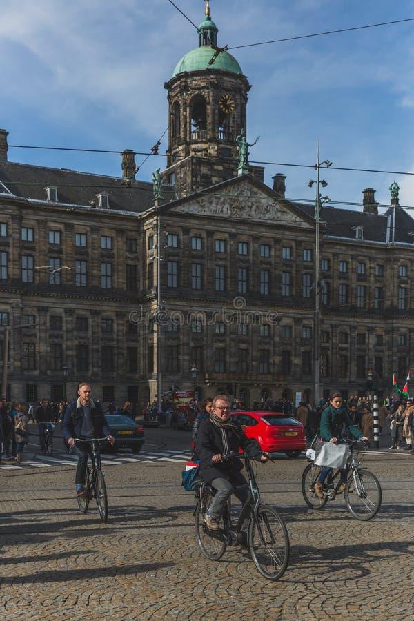 骑自行车通过奥斯陆王宫阿姆斯特丹的本机 免版税图库摄影