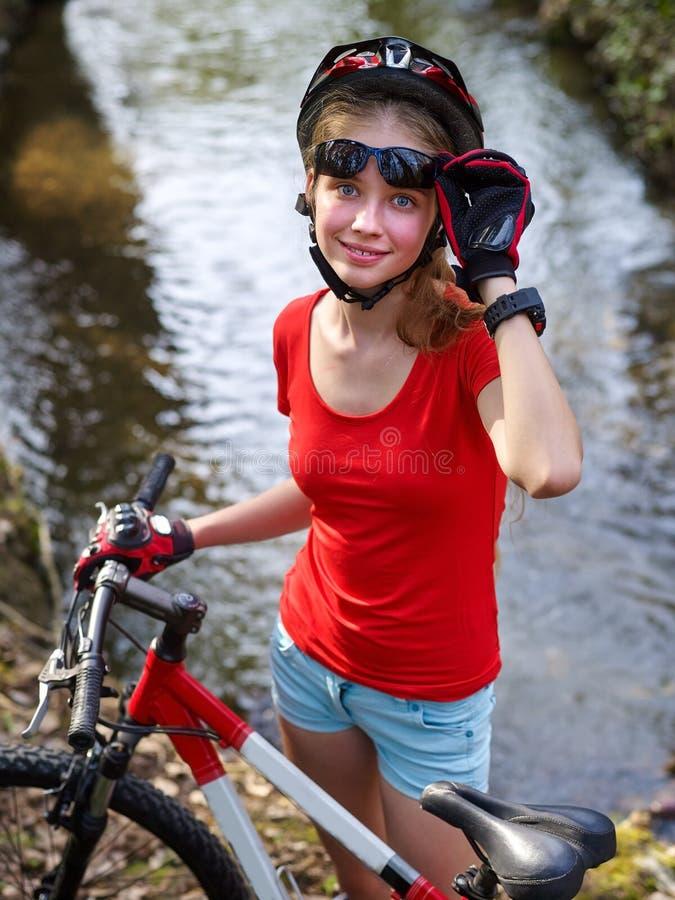 骑自行车骑自行车的女孩循环的涉过在水中 免版税库存照片