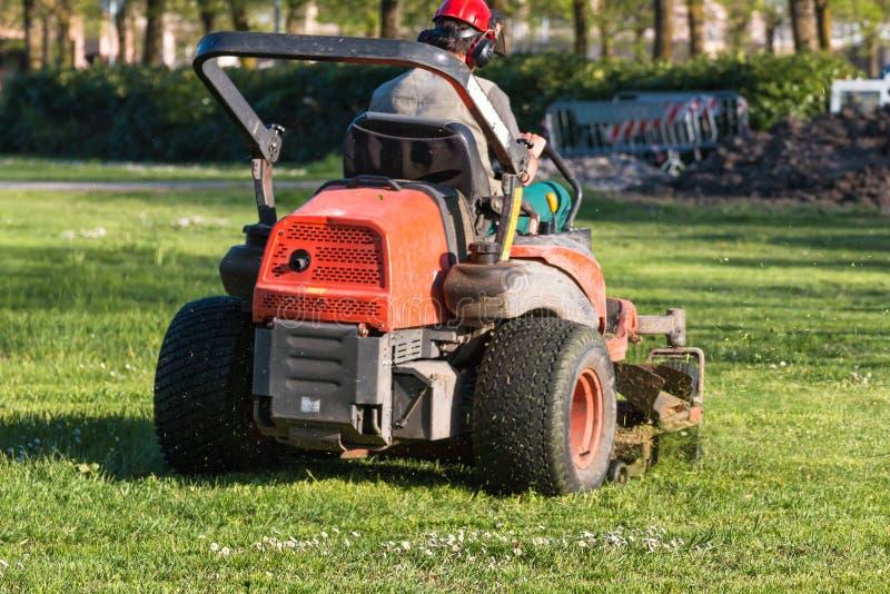 骑马有操作员的草坪设备 免版税库存照片