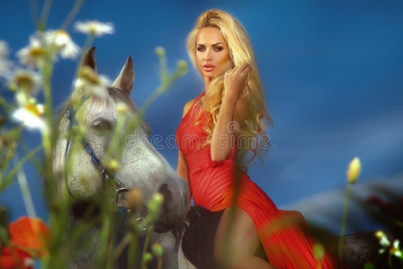 骑马的可爱的白肤金发的女孩时兴的照片。 免版税库存照片