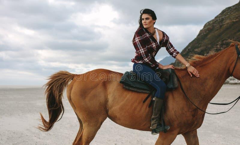 骑马的女孩在海岸线 免版税库存图片