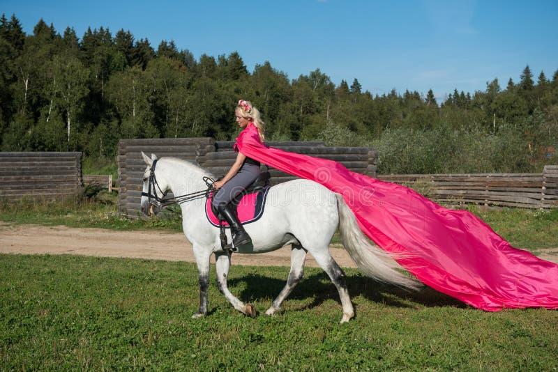 骑马的白肤金发的妇女 免版税库存照片