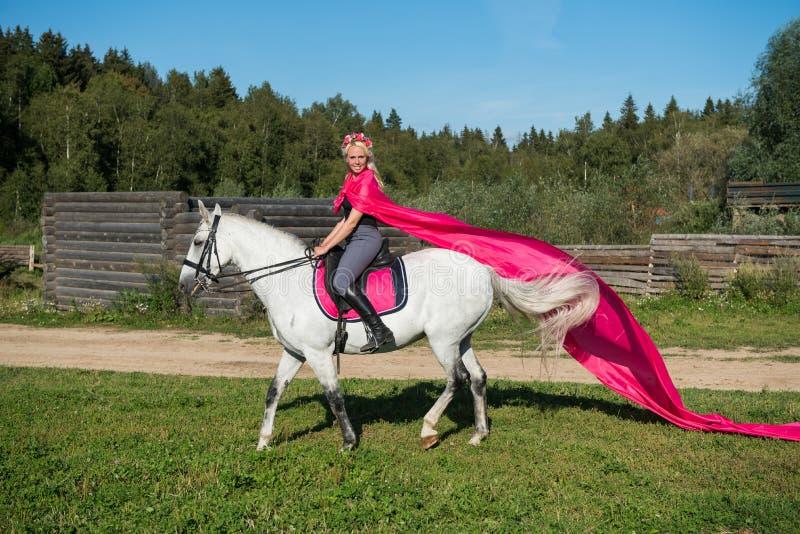 骑马的白肤金发的妇女 图库摄影