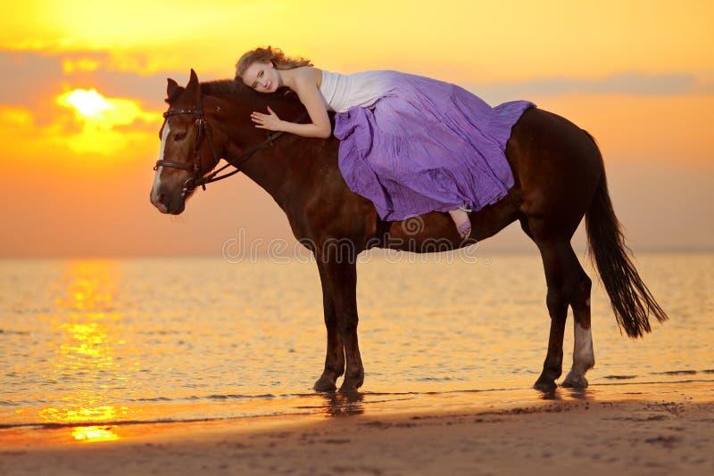 骑马的美丽的妇女在日落在海滩 年轻bea 免版税库存图片