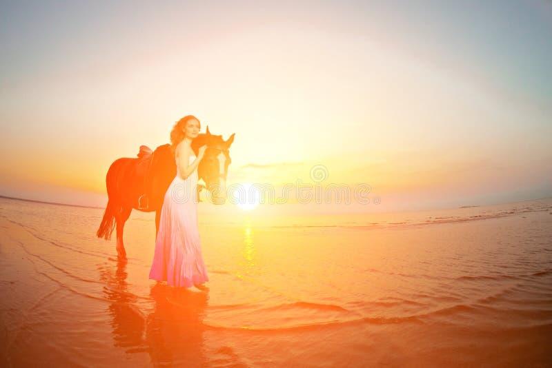骑马的美丽的妇女在日落在海滩 年轻gir 图库摄影