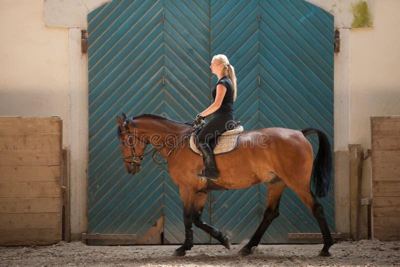 骑马的美丽的年轻白肤金发的妇女 库存图片
