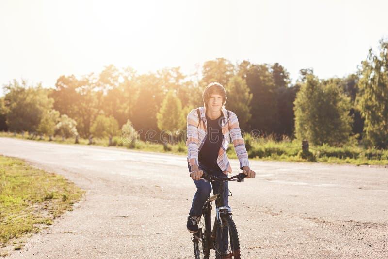 骑他的自行车的逗人喜爱的十几岁的男孩佩带的衬衣运载的背包有休息在他的乘驾期间在城市的郊区 在男小学生射击工作室空白年轻人的背景 免版税库存图片