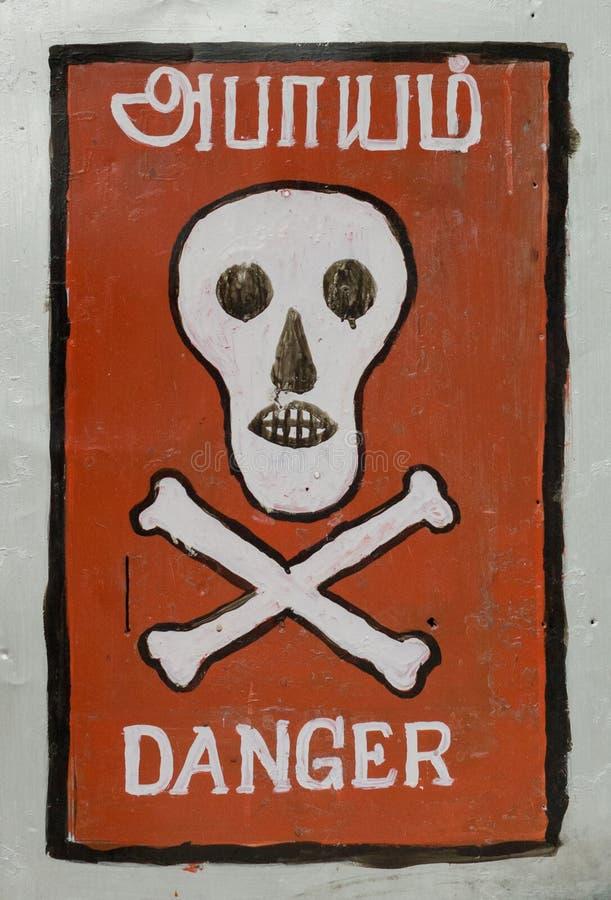 头骨和骨头危险签到泰米尔语和英语 免版税库存图片