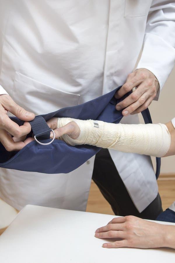 骨科医师医生在被包扎的妇女的手上把吊索放 免版税图库摄影