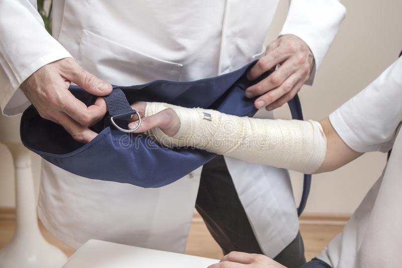 骨科医师医生在被包扎的妇女的手上把吊索放 图库摄影