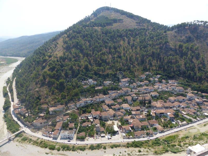 高一个看见的山的底部的村庄与在河附近 培拉特 通风 免版税库存照片