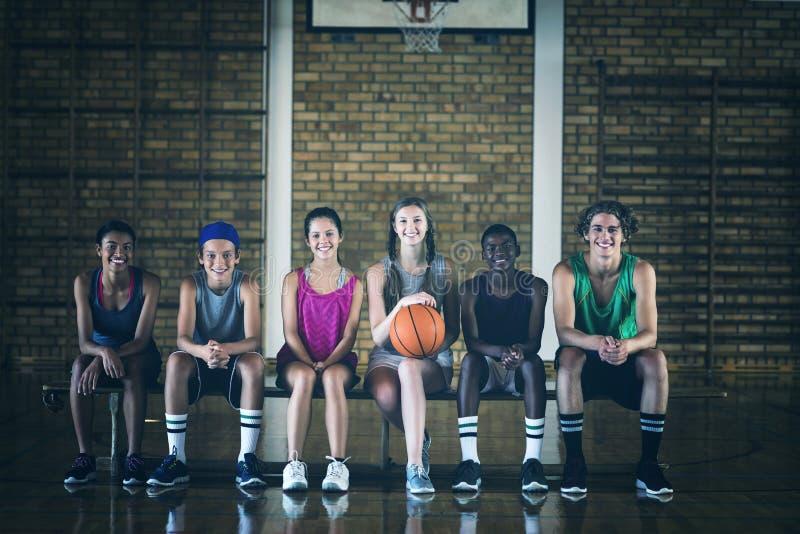 高中哄骗坐在篮球场的一条长凳 库存照片