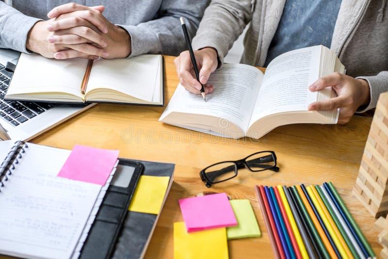 高中坐在书桌的家庭教师或大学生小组在读的图书馆里学习和,做家庭作业和教训实践 库存图片