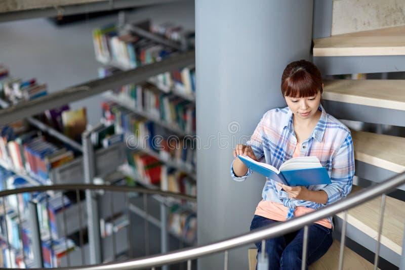 高中学生女孩在图书馆的阅读书 图库摄影