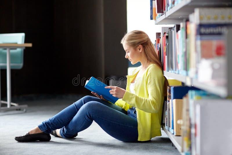 高中学生女孩在图书馆的阅读书 库存照片