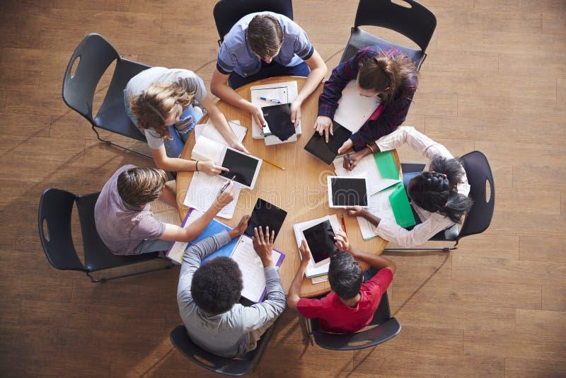 高中学生顶上的射击使用数字式片剂的在小组研究在表附近 免版税库存图片