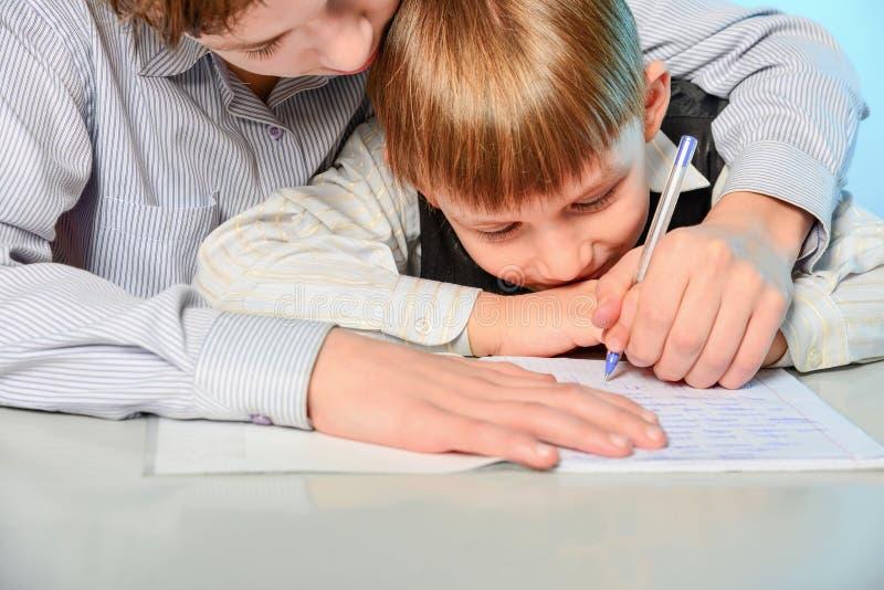高中生准备第一辆平地机以书面方式和为学校做准备 哥哥教更加年轻 免版税图库摄影