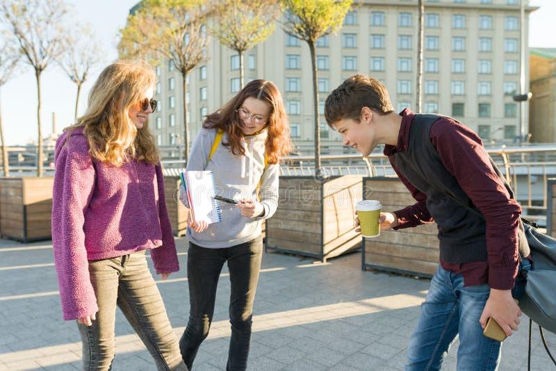 高中生是谈话室外 女孩在干净的白色板料的少年陈列在看笔记本的笔记本和男孩 库存图片
