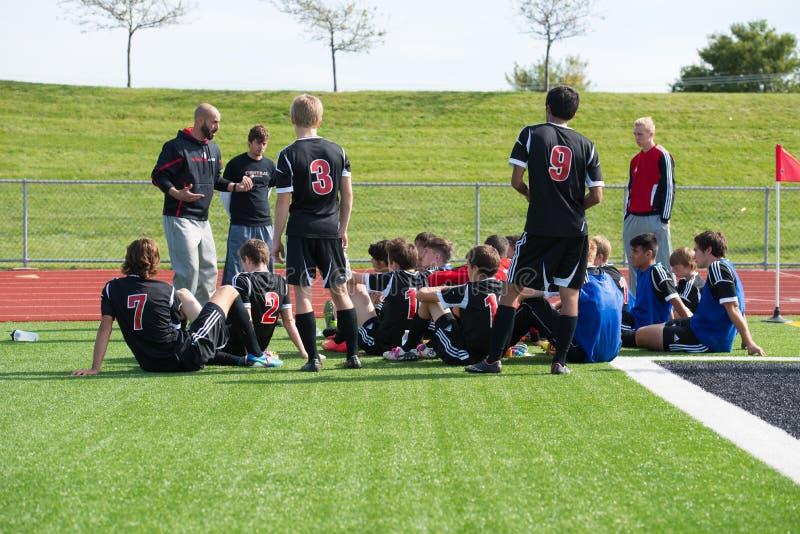 高中足球教练与他的队谈话 免版税库存图片