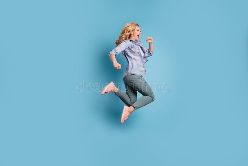 高兴人呼喊的佩带的裤子长裤外形边全长照片被隔绝在蓝色背景 库存图片